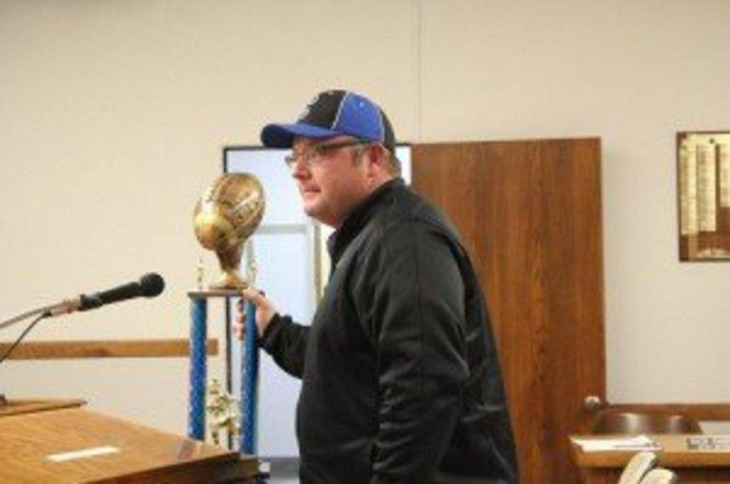 Coach Todd Oldham displays the Championship trophy that Team Us 11/12 year old traveling football team from Price won in Mesquite Nov 23